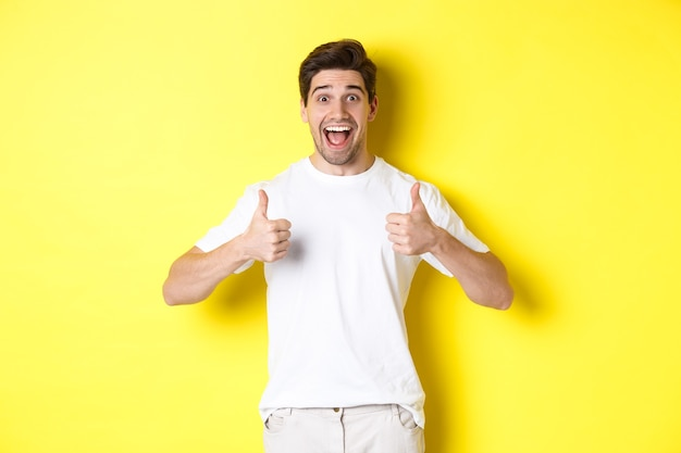 Excited handsome man showing thumbs up, approve and saying yes, standing over yellow background.