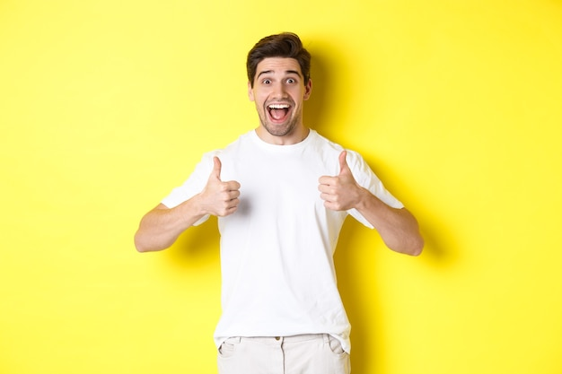 Excited handsome man showing thumbs up, approve and saying yes, standing over yellow wall