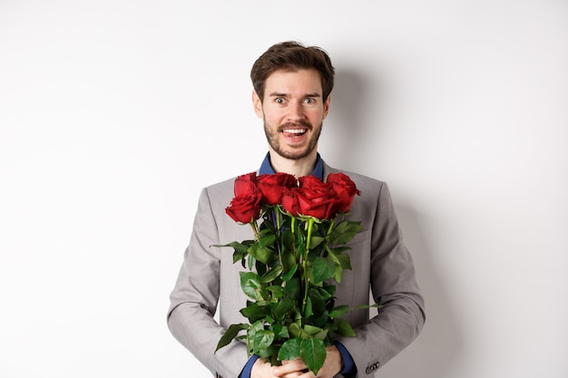 Excited handsome man in suit holding bouquet of roses for romantic date with lover, standing happy on valentines day, white background.