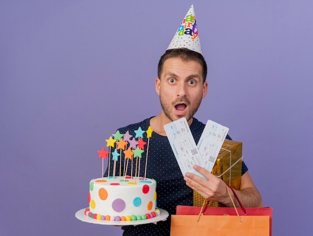 Eccitato bell'uomo che indossa il berretto di compleanno tiene il contenitore di regalo del sacchetto della spesa di carta della torta di compleanno e biglietti aerei isolati sulla parete viola
