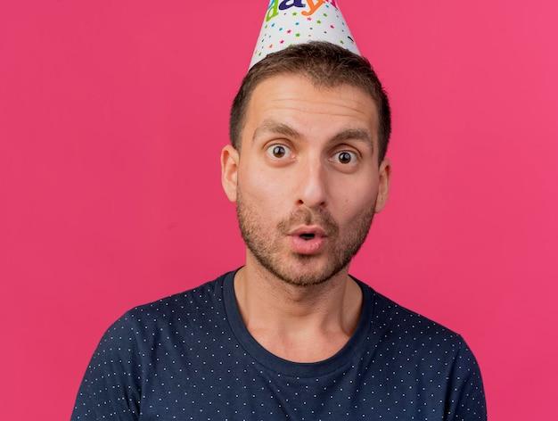 생일 모자를 쓰고 흥분된 잘 생긴 남자가 복사 공간이 분홍색 벽에 고립 된 앞에 보인다