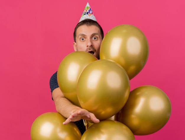 Eccitato berretto da portare di compleanno dell'uomo bello sta dietro i palloncini dell'elio che allungano la mano isolata sulla parete rosa con lo spazio della copia