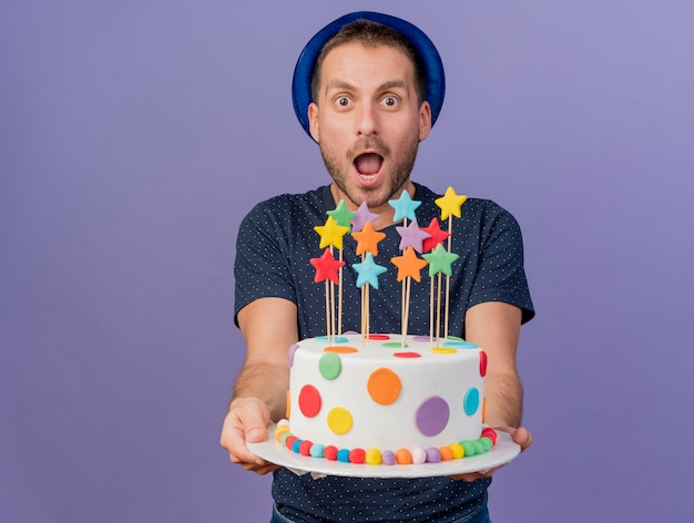 Excited handsome man wearing blue hat holds birthday cake looking at front isolated on purple wall