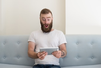 Excited handsome man with tattoo watching video on tablet