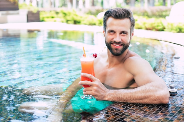 Excited handsome modern muscular man is resting in summer pool and drinks refreshing cocktail and looks on camera.