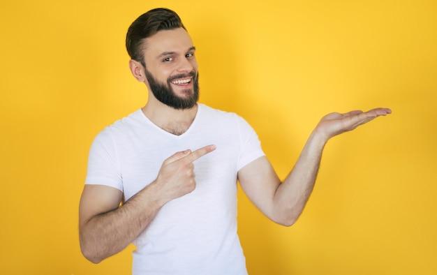 Возбужденный красивый молодой бородатый мужчина в белой футболке указывает в сторону