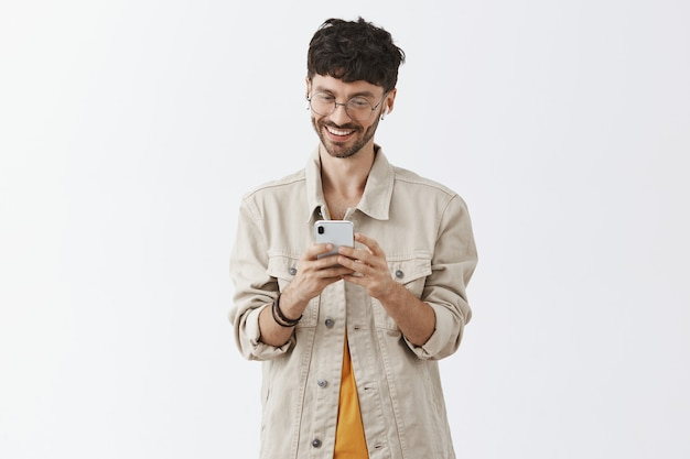 Excited handsome young man using mobile phone and looking happy