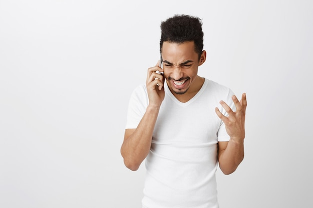 Взволнованный счастливый афро-американский мужчина разговаривает по телефону и весело улыбается