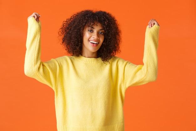 アフロヘアカットで興奮した幸せなアフリカ系アメリカ人の少女は、興奮と幸福から手を上げ、勝利を応援し、勝利を祝います。