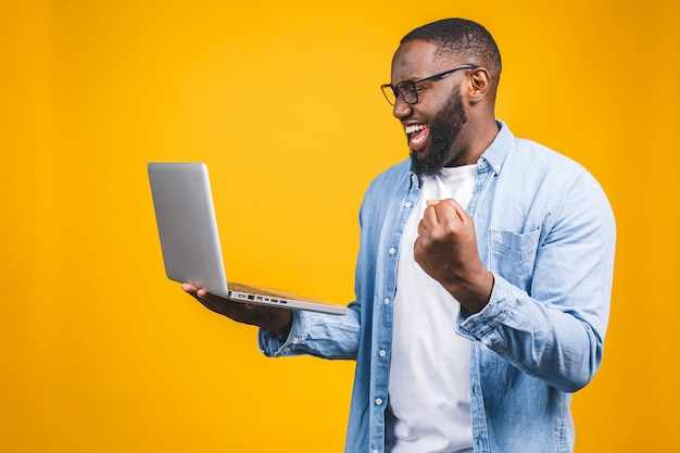 Excited happy afro american man looking at laptop computer screen and celebrating the win