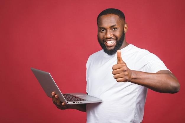 コンピューターの画面と赤い背景に分離された勝利を祝って興奮して幸せなアフロアメリカンの男。いいぞ。
