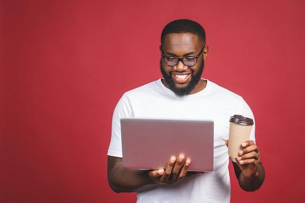 Excited счастливый афро американский человек с экраном компьютера, кофе или чаем, празднуя победу изолированную над красной предпосылкой.