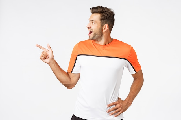 Excited, happy amused masculine sportsman in active wear, attend gym