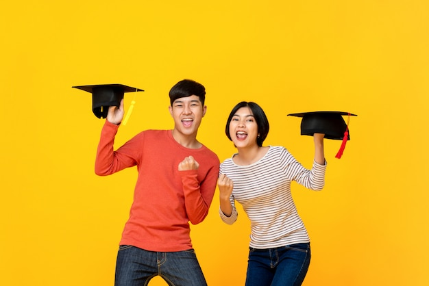 Excited happy asian college students in yellow studio background