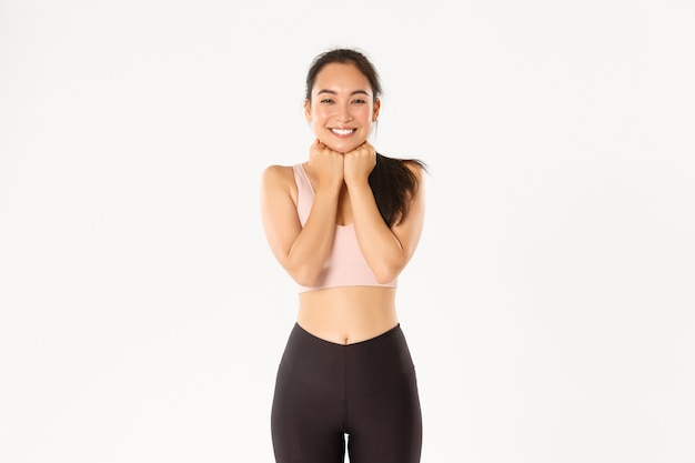 Excited and happy asian fitness girl in activewear looking amused, cant wait try something, standing tempting over