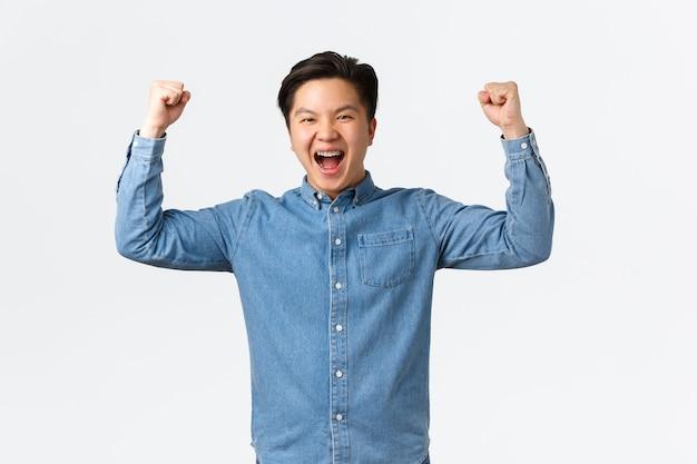 Eccitato uomo asiatico felice con bretelle che sente successo per aver vinto il premio, pompa a pugno e gridando sì, gioendo, trionfando come campione, in piedi sfondo bianco che celebra.