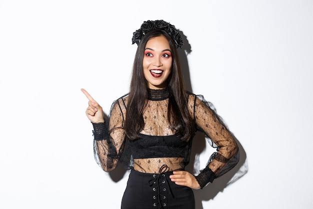 Excited happy asian woman in black lace dress and wreath looking amazed at upper left corner, pointing finger at your halloween promo banner, standing over white wall