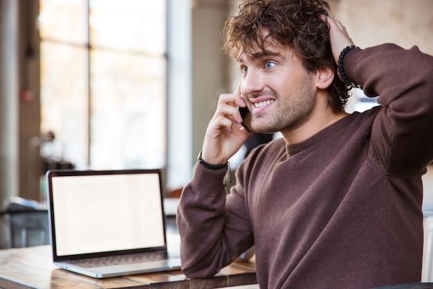 興奮した幸せな魅力的な陽気なコンテンツ携帯電話で話し、ラップトップで作業する楽しいハンサムな巻き毛の男