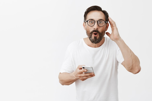 Excited and happy bearded mature man posing with his phone