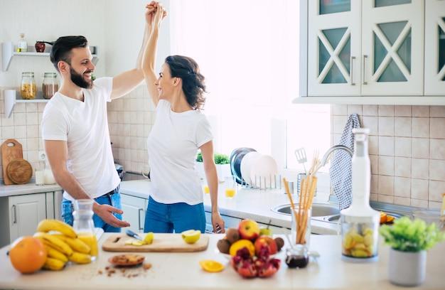 Взволнованная счастливая красивая молодая пара в любви готовит на кухне и веселится вместе, танцуя и улыбаясь