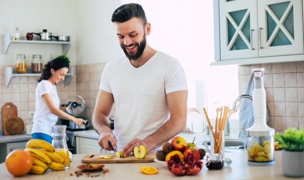 Взволнованная счастливая красивая молодая влюбленная пара готовит на кухне и веселится вместе, делая салат из свежих здоровых фруктов
