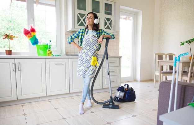 Excited and happy beautiful young woman in an apron is cleaning the floor in her kitchen at home and dancing