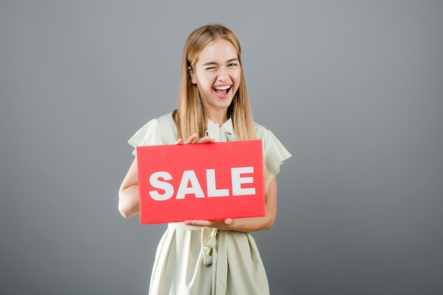 Excited happy beautiful young woman with sale sign isolated over grey