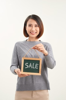 Excited happy beautiful young woman with sale sign isolated over white