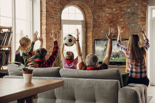 興奮した、幸せな大家族チームが自宅のソファで一緒にスポーツの試合を見る