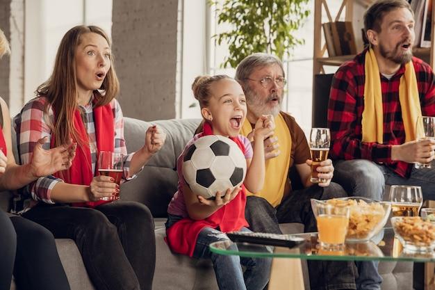 Взволнованная, счастливая большая семья смотрит футбол, футбольный матч на диване у себя дома. болельщики эмоционально болели за любимую сборную. развлекается от бабушки и дедушки к детям. спорт, тв, чемпионат.