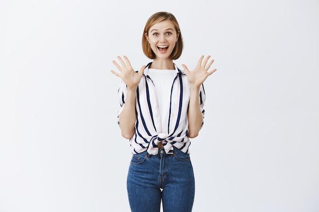 Возбужденная счастливая белокурая девушка выглядит удивленной и обрадованной отличными новостями
