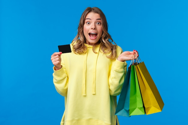 Excited happy blond girl ready waste all money on her bank account, scream thrilled and joyful during shopping, holding bags with goods and credit card, stand blue
