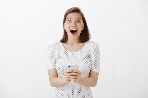 Взволнованная счастливая белокурая женщина получает отличные новости по мобильному телефону, удивленно улыбаясь