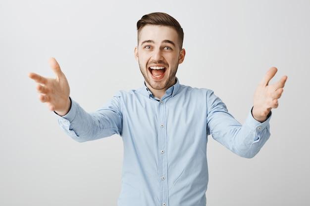 興奮して幸せなビジネスマンが誰かに挨拶するために手を差し伸べて、賞を受賞し、製品を保持