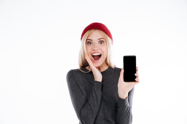 Excited счастливая вскользь молодая женщина показывая мобильный телефон пустого экрана