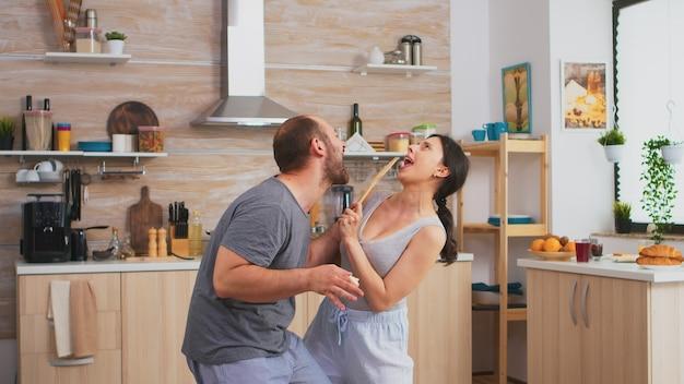 朝食時にパジャマを着てキッチンで踊る興奮した幸せなカップル。のんきな妻と夫が笑って楽しんで面白い人生を楽しんでいる本物の既婚者ポジティブ幸せな関係