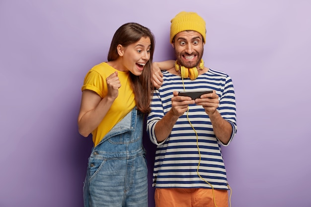 Excited happy couple use mobile phone for playing online games, look impressively at smartphone device, being obssessed with modern technologies, dressed in fashionable clothes. internet addiction