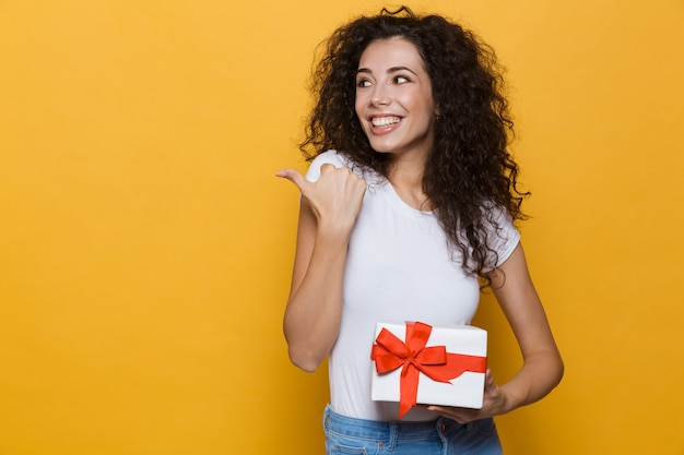 Excited happy cute young woman posing isolated on yellow holding gift box present pointing.