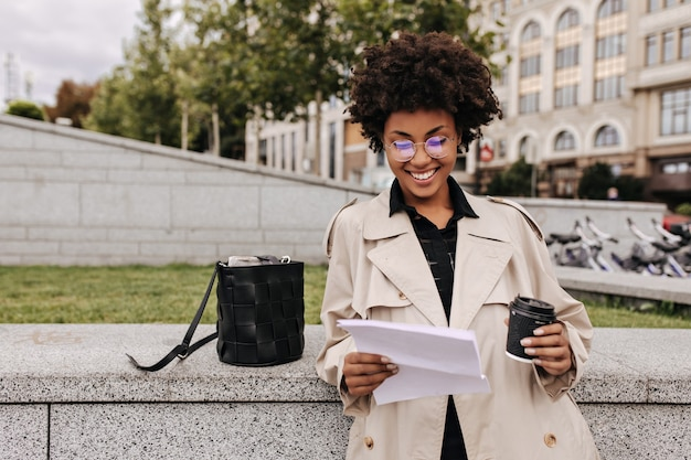 Excited happy dark-skinned woman in beige trench coat and eyeglasses smiles, holds paper sheets and coffee glass outside