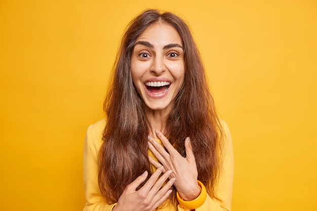 Excited happy european woman with natural long hair smiles broadly hears excellent news
