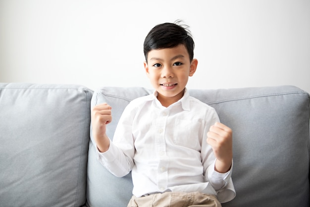 Excited and happy family and son with arms raised while watching television at home