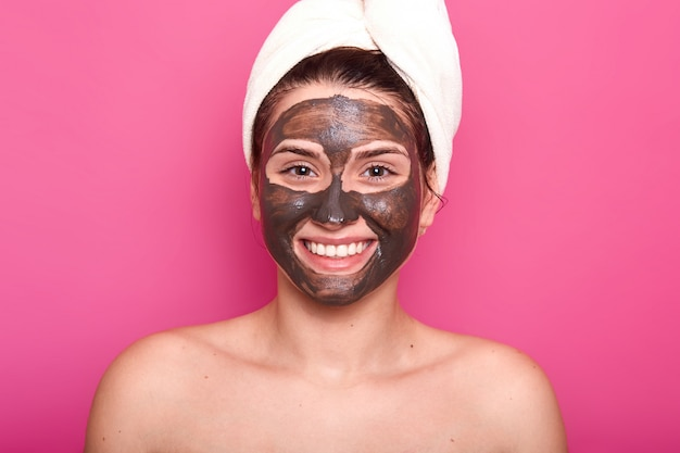 Excited happy female poses with toothy smile and chocolate facial mask, with naked shoulders, takes care of her beauty and appearance, wears white towel on head, isolated over pink wall.