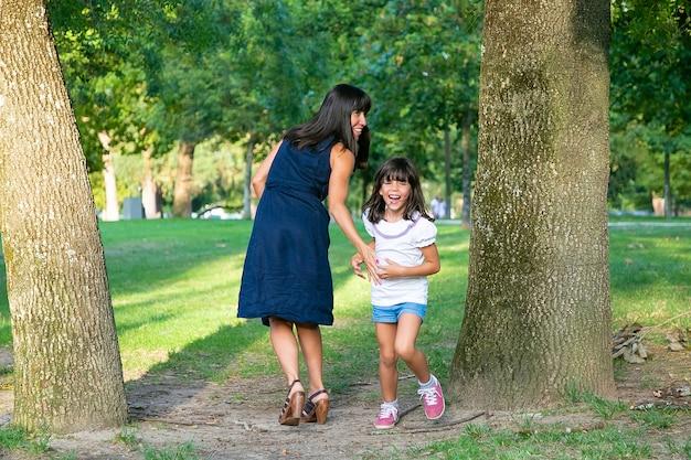 Ragazza felice eccitata che gioca giochi attivi con sua madre all'aperto, in piedi sugli alberi nel parco e ridendo. lunghezza intera. famiglia attività all'aperto e concetto di svago