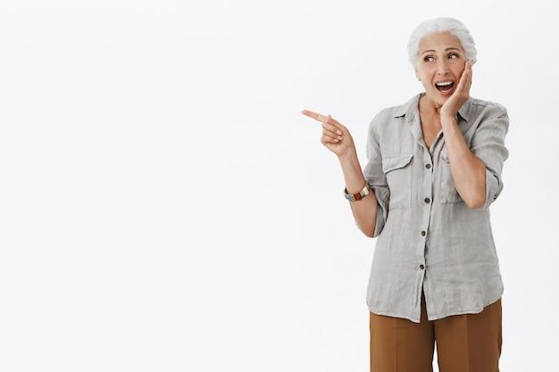 왼쪽 손가락을 가리키고 놀란 웃는 흥분된 행복 할머니