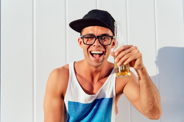 Excited happy guy in sunglasses and cap holds a bottle of beer, smiling widely