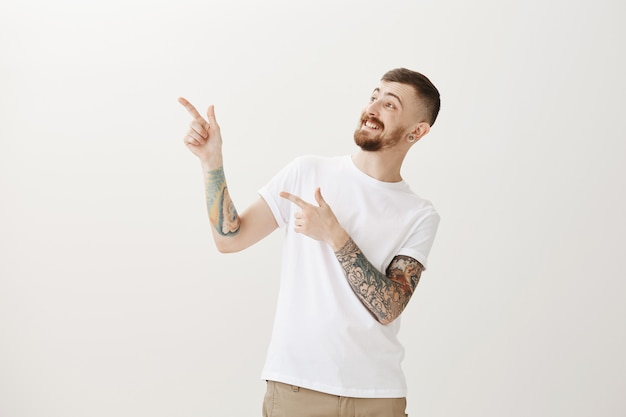 Excited happy hipster guy pointing and looking upper left corner amazed