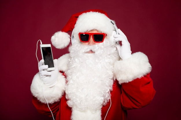 Excited happy hipster santa claus in headphones and sunglasses is having fun on the party