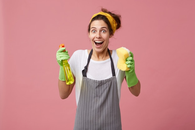 Взволнованная счастливая домохозяйка в желтом шарфе на голове и фартуке держит спрей с губкой, глядя с широко открытыми глазами и ртом