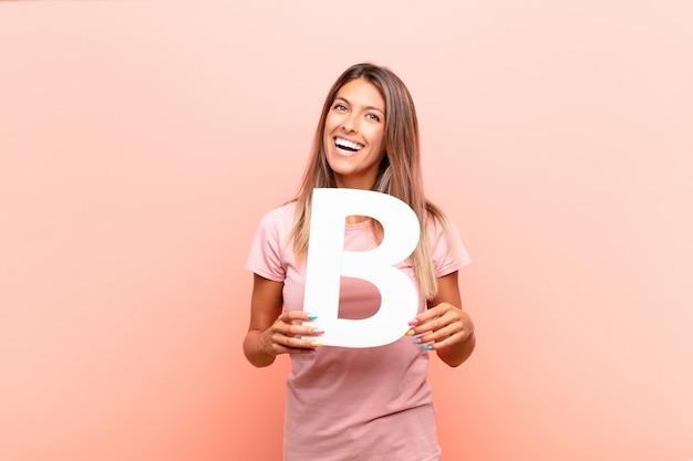 Возбужденный, счастливый, радостный, держа букву b алфавита, чтобы сформировать слово или предложение.