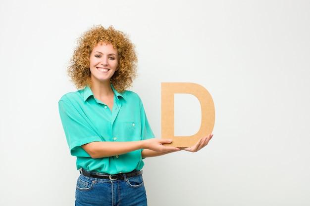 Возбужденный, счастливый, радостный, держа букву d в алфавите, чтобы сформировать слово или предложение.